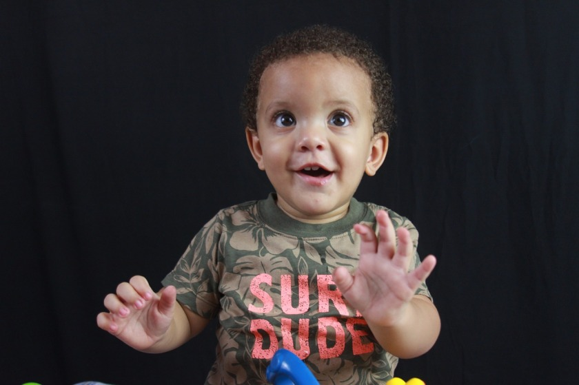 "Image is of a toddler boy smiling with his hands in the air. He is wearing a shirt that says ""Sure dude."""