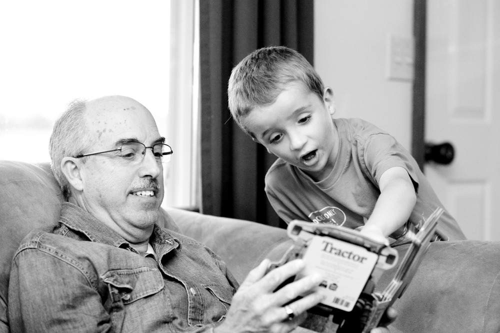 Black and white image of a boy looking at a book with his grandfather. The grandfather is a sitting in an armchair holding the book, and the boy is leaning over the edge of the chair and pointing to something on the page.