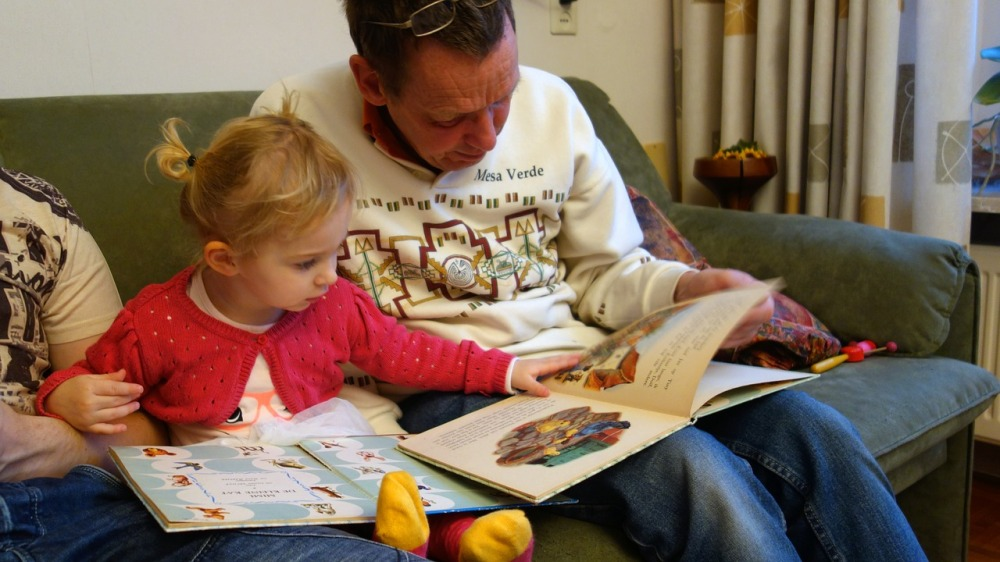 Image is of a toddler girl reading a book with her father.